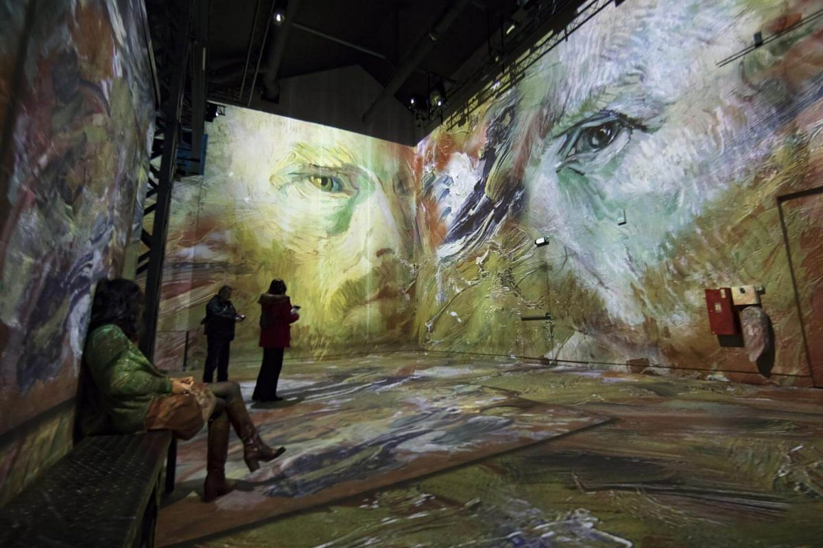 Visitors look at works by Dutch painter Vincent Van Gogh that are projected onto walls at the Atelier des Lumieres.