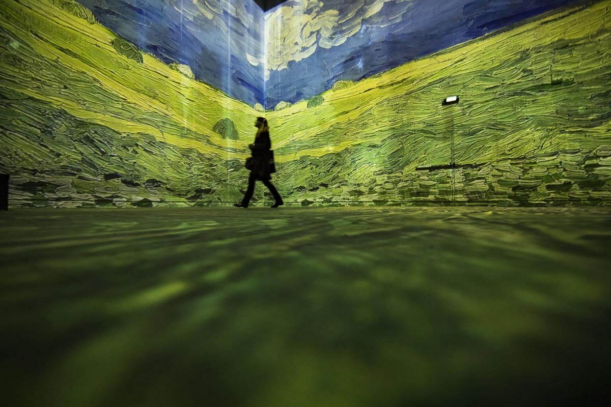 A visitor looks at a painting by Van Gogh that is projected onto walls at the Atelier des Lumieres.