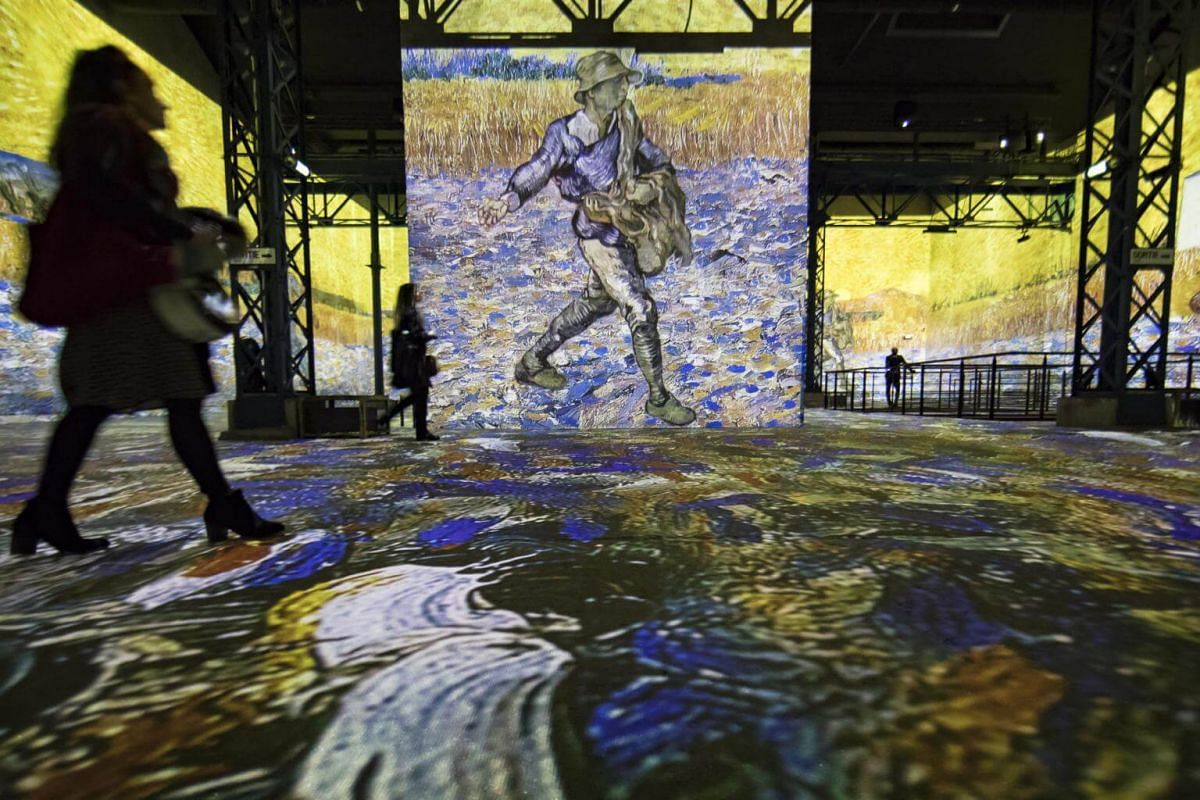 "Visitors look an image of Van Gogh's ""The Sower"" that is projected onto walls at the Atelier des Lumieres."