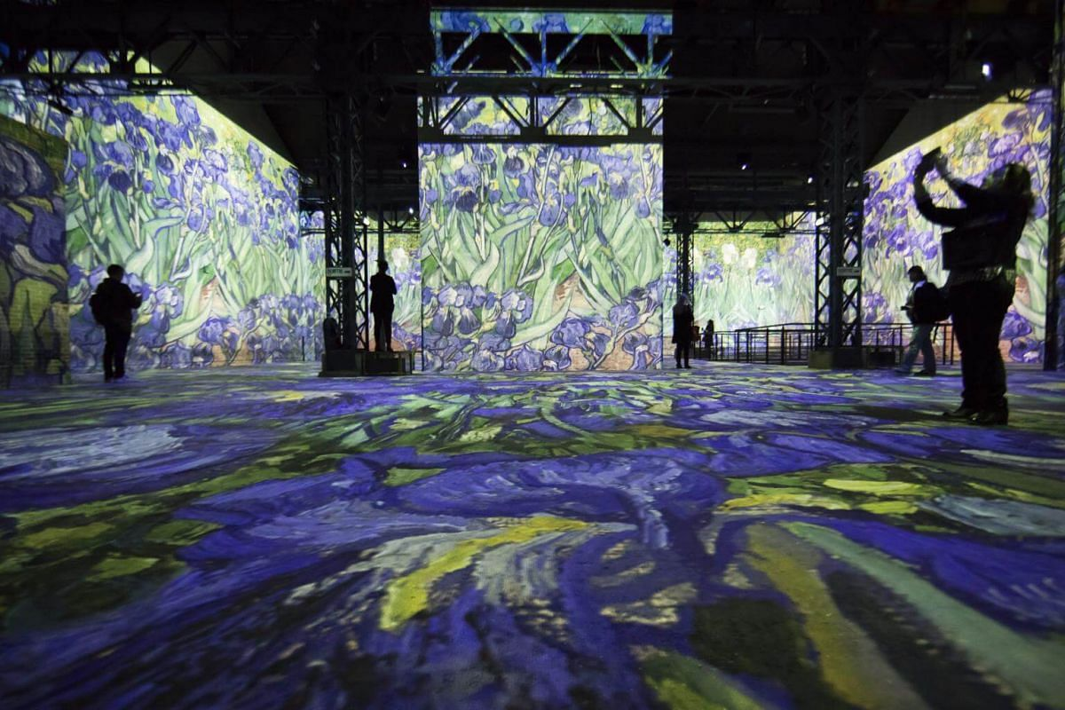 "Visitors wander through ""Irises"" projected onto walls at the Atelier des Lumieres."