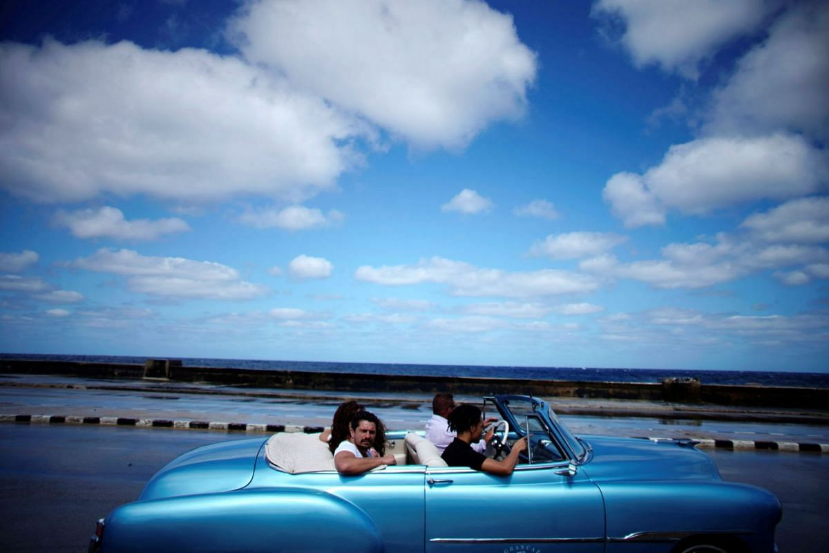 Tourists ride in a vintage car at the seafront Malecon in Havana, Cuba, March 6, 2019. PHOTO: REUTERS