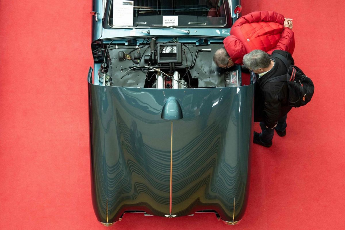 Visitors inspect the engine of an Aston Martin DB 2/4 car at the Retro Classics 2019 vintage car fair in Stuttgart, southern Germany, on March 7, 2019. - The fair is running until March 10, 2019. PHOTO: AFP