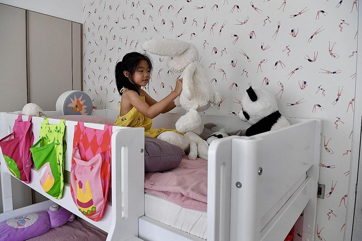 For their three daughters' bedroom, Ms Frances Yeap and Mr Darrell Ee chose a wallpaper featuring yoga poses. In the photo is their eldest daughter, Emma, seven.