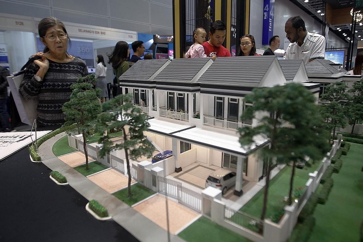 Home buyers checking out a housing expo early this month in Kuala Lumpur, where 180 developers offered 22,000 housing units priced at RM300,000 or less. Developers were asked to offer at least a 10 per cent discount, and the government will exempt st