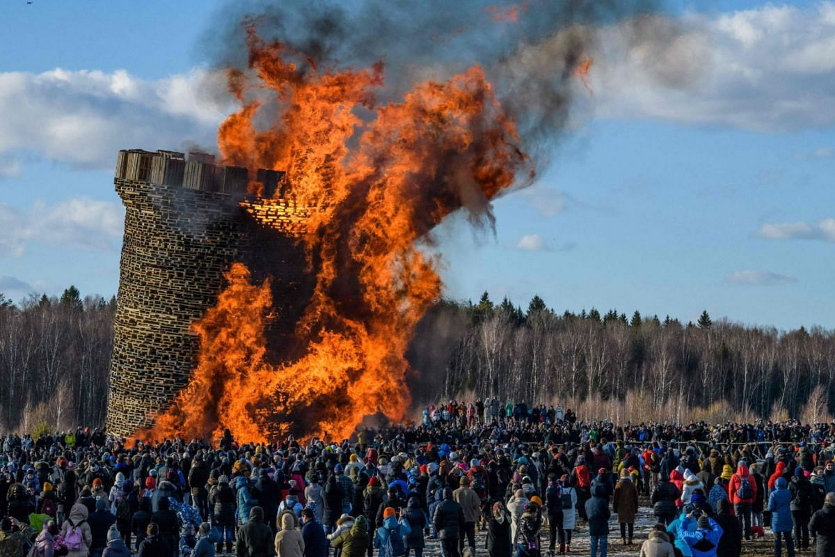 Spectators watch the burning of a 20m high structure built of wood pallets and representing the Bastille fortress, the symbol of the 1789 French Revolution, as Russians celebrate Maslenitsa, the eastern Slavic Shrovetide in the village of Nikola-Leni