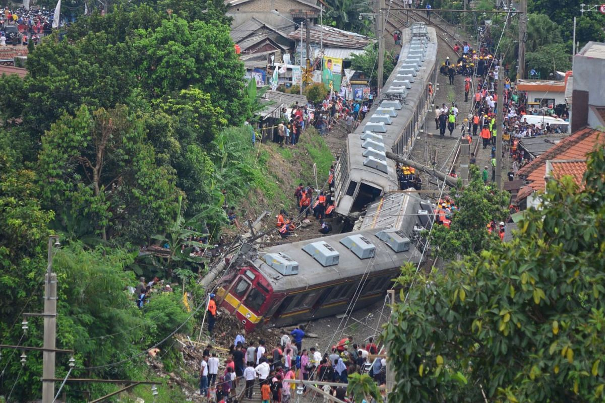 An Indonesian search and rescue team examine a train after it derailed in Bogor on March 10, 2019. Several people were injured and no fatalities were reported in the accident. PHOTO: AFP