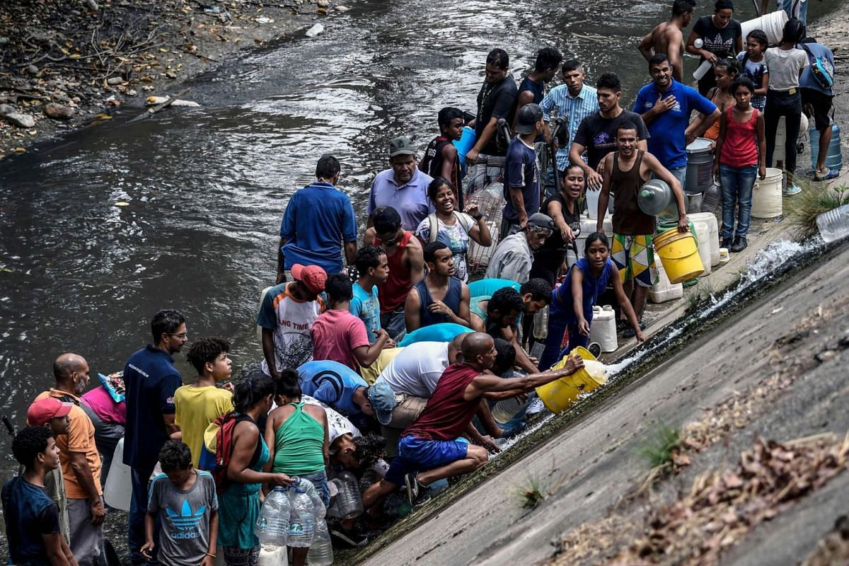 People collect water from a sewage canal at the river Guaire in Caracas on March 11, 2019, as a massive power outage continues to affect some areas of the country. Venezuela's opposition leader Juan Guaido has asked lawmakers on Monday to declare a ""