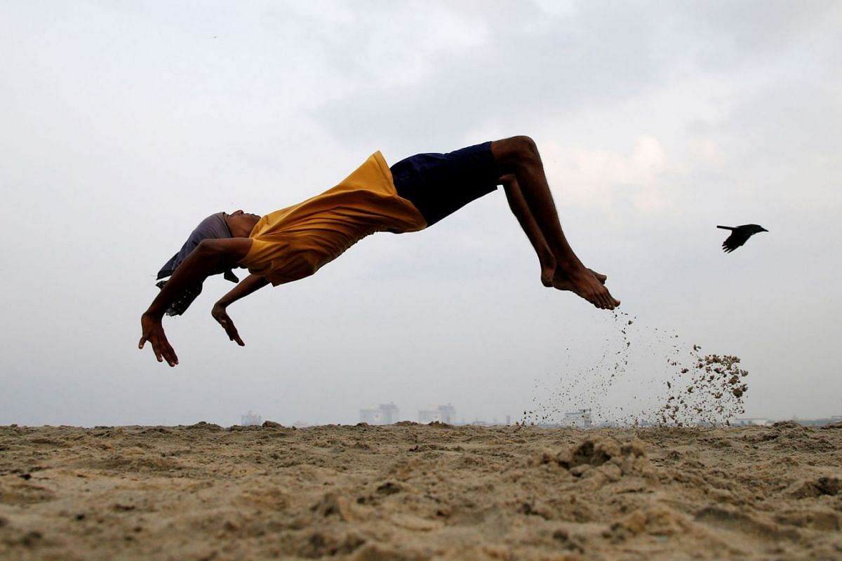 A boy practices somersaulting as he exercises at a beach in Kochi, India, March 11, 2019. PHOTO: REUTERS