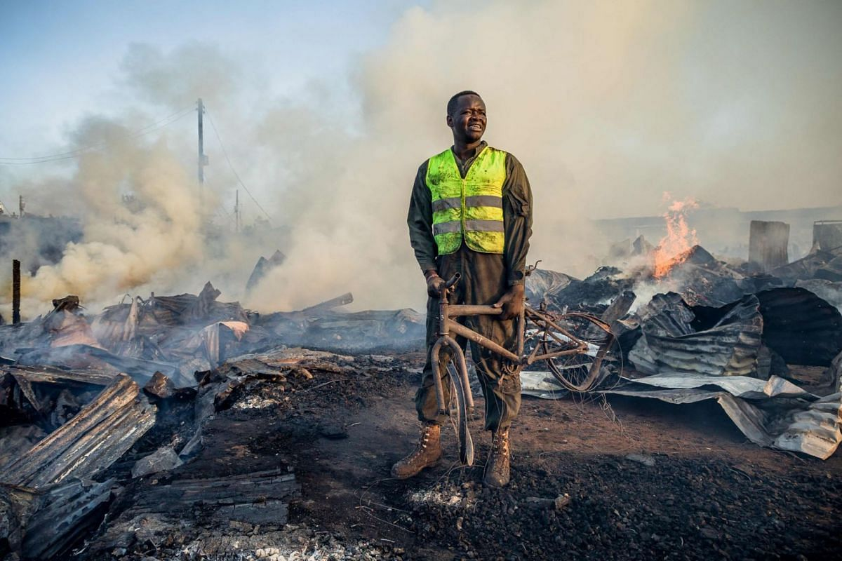 A resident who helps firefighters holds a burnt bicycle after a fire at Toi Market selling second hand clothes at a Kibera slum in Nairobi, Kenya, on March 12, 2019. PHOTO: AFP