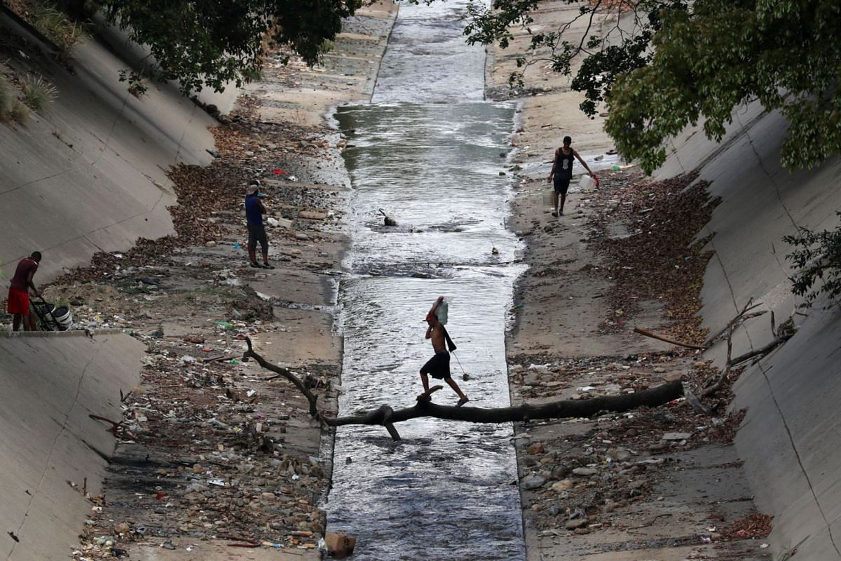 A local carries a water container as he crosses a canal in Caracas, Venezuela on March 12, 2019. PHOTO: REUTERS