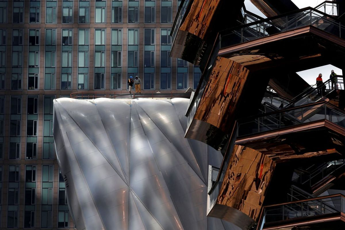 """Workers are seen on """"The Vessel"""" (R) comprised of 154 connected flights of stairs and 80 landings designed by English designer, Thomas Heatherwick and on """"The Shed"""" arts center (L) at the Hudson Yards development on Manhattan's West side, in New York"""