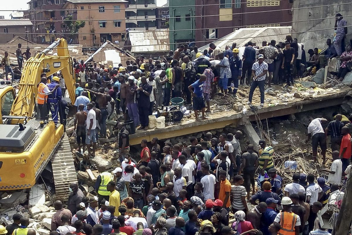 Rescue workers at the scene of a building collapse in Ita Faji, Lagos, Nigeria, March 13, 2019. Reports indicate the three story building contained a primary school on its top floor. Rescue workers are working to free trapped pupils from the rubble.