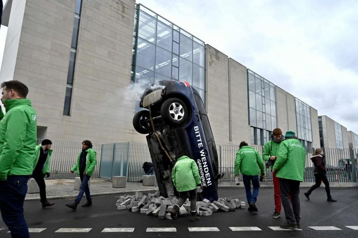 Activists from the environmental group Greenpeace display an overturned car during a protest action outside the Chancellery where a meeting on the climate protection in the transport sector takes place on Mar 14, 2019 in Berlin, Germany. PHOTO:AFP