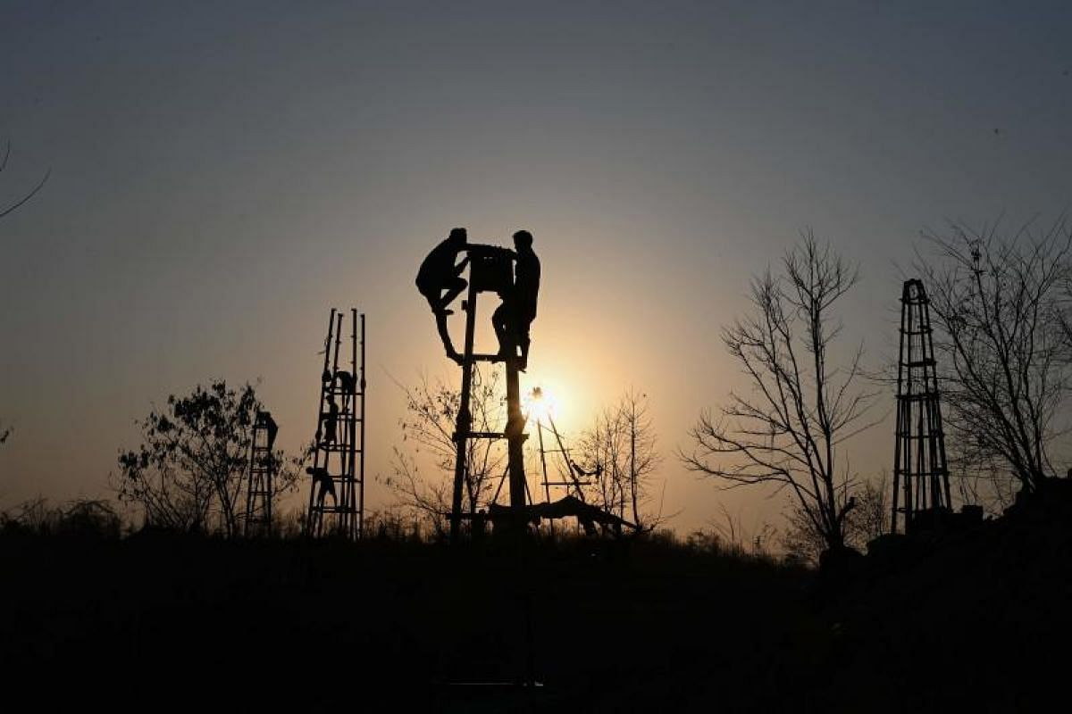 This photo shows workers building a new oil rig at an informal oil field in Minhla township, central Myanmar. The fields near Minhla are Myanmar's equivalent of the old American Wild West, where informal oil entrepreneurs scramble from site to site i