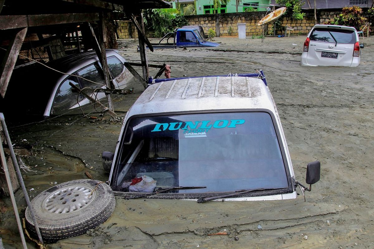Cars are submerged in mud following a flash flood in Sentani, Papua, Indonesia, March 17, 2019. The flood has killed at least 61 people as rescuers race to help dozens of other victims of the disaster. Dozens have been injured and more than 4,000 peo