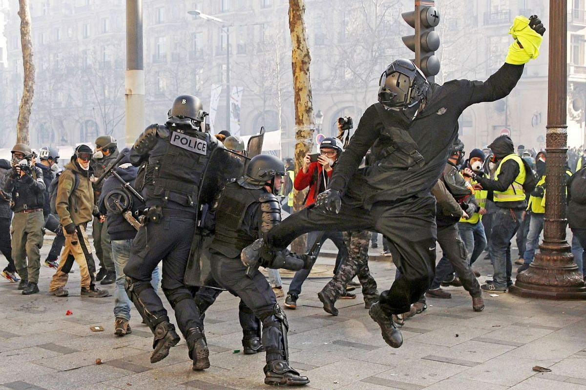 A Yellow Vest protester kicks a riot police officer on the Champs Elysees during the 'Act XVIII' demonstration (the 18th consecutive national protest on a Saturday) in Paris, France, March 16, 2019. The so-called 'gilets jaunes' (yellow vests) is a g