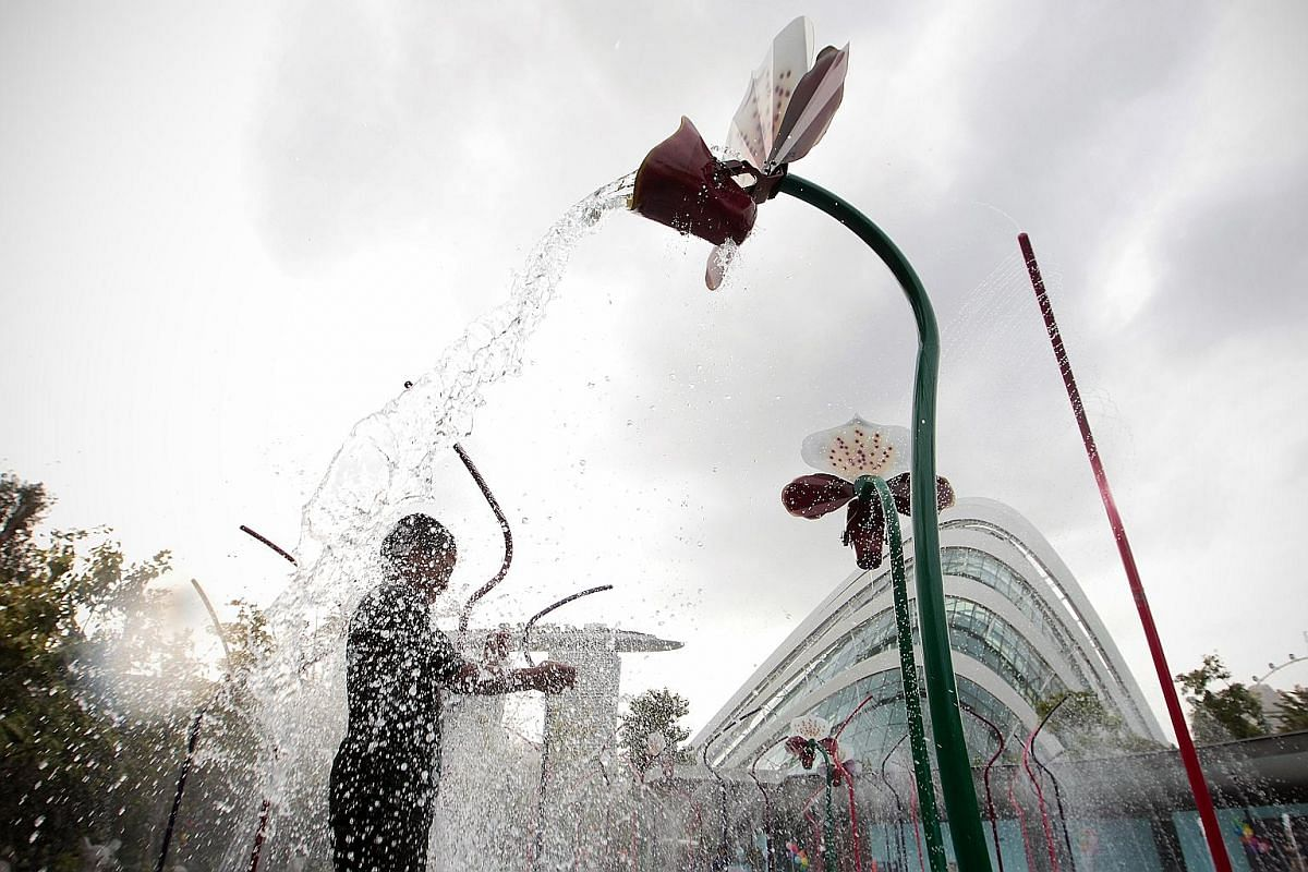 Right: A boy playing under a curtain of water falling from orchid-shaped splash buckets at the Waterplay area at the Far East Organization Children's Garden at Gardens by the Bay. Far right: A participant at the TRI-Factor Series triathlon held at th