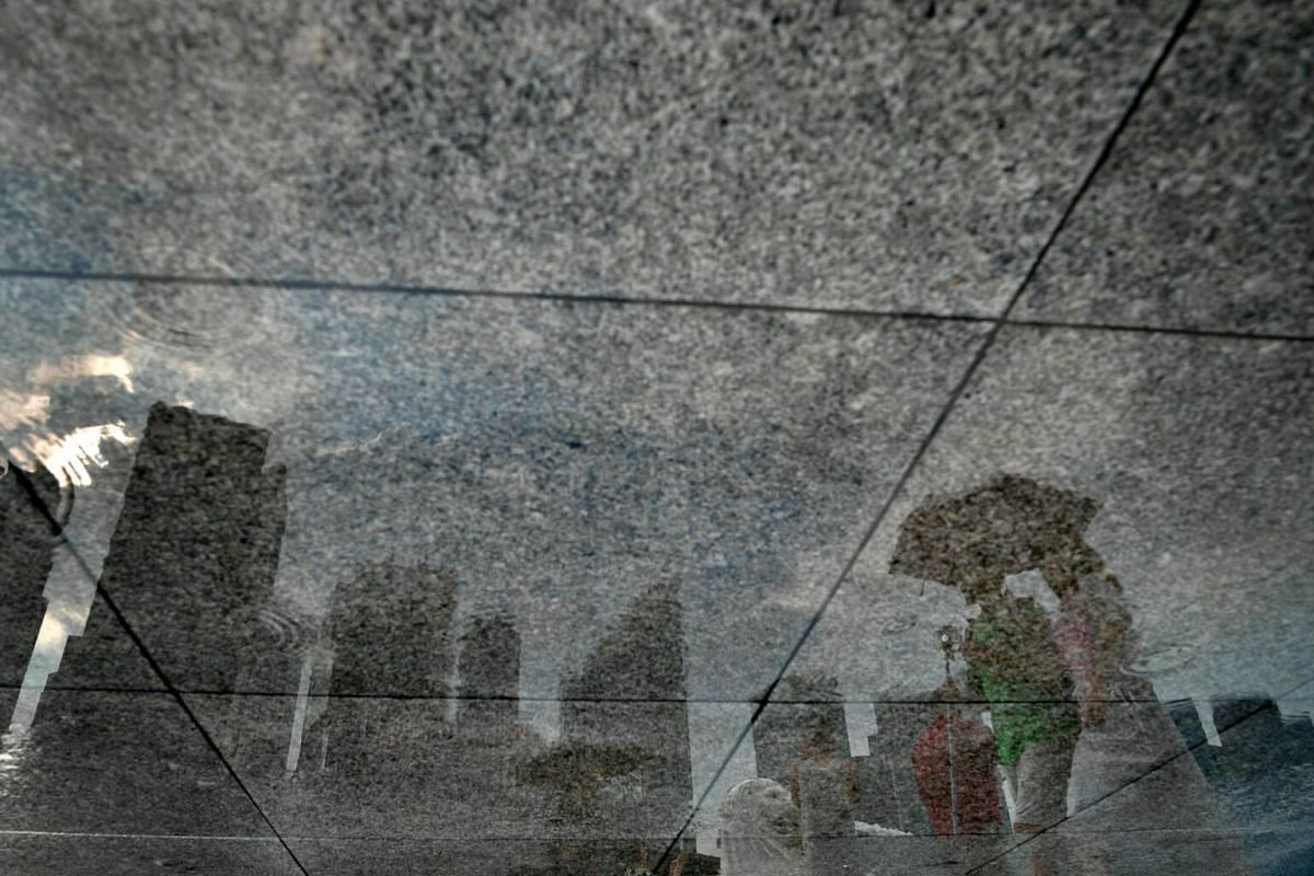 Reflection of the skyline, the Merlion and people carrying umbrellas, in the puddle of water on the ground after a light shower on Nov 17, 2016.