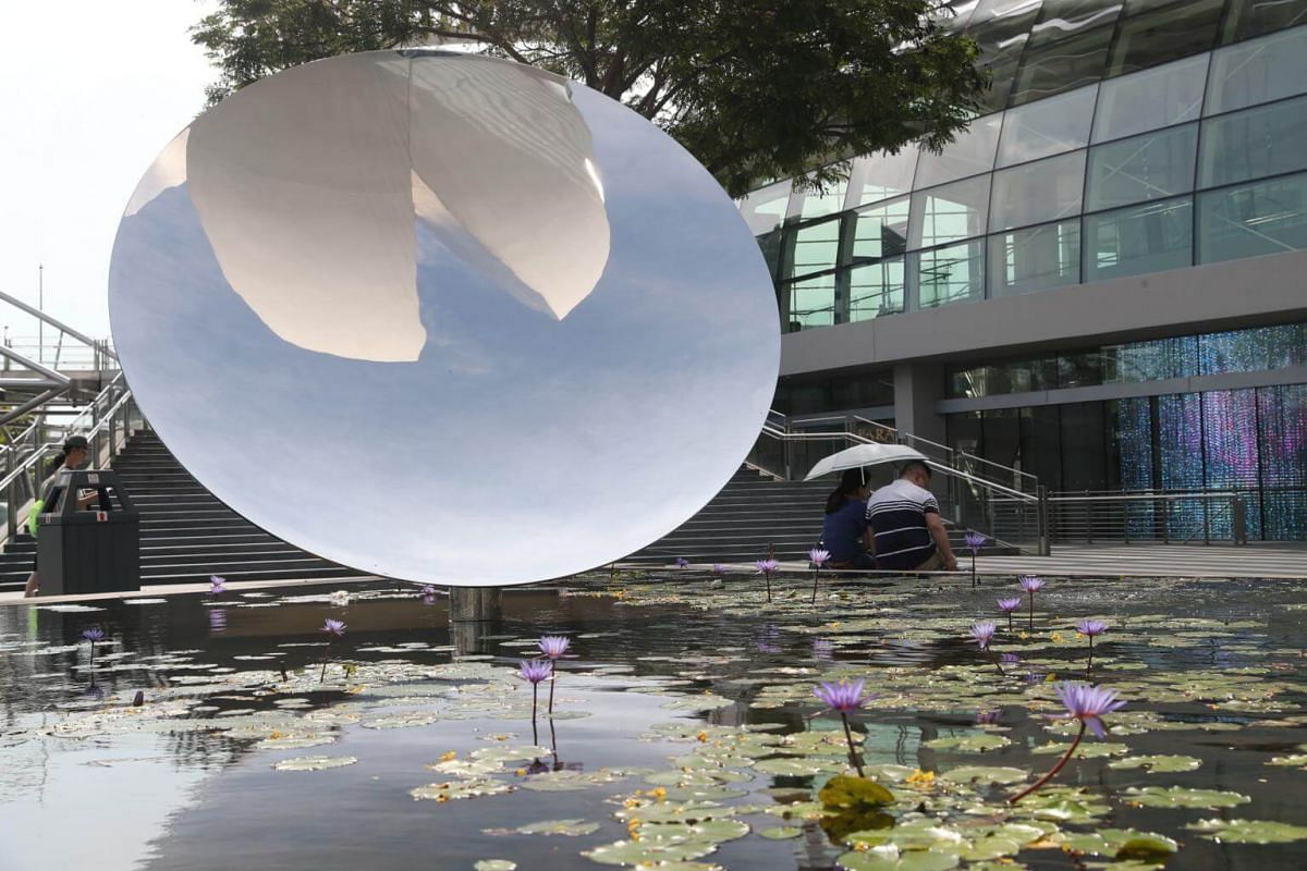 A couple seated by the Marina Bay Sands Lotus Pond as the inverted reflection of the ArtScience Museum is seen on a concave mirror.