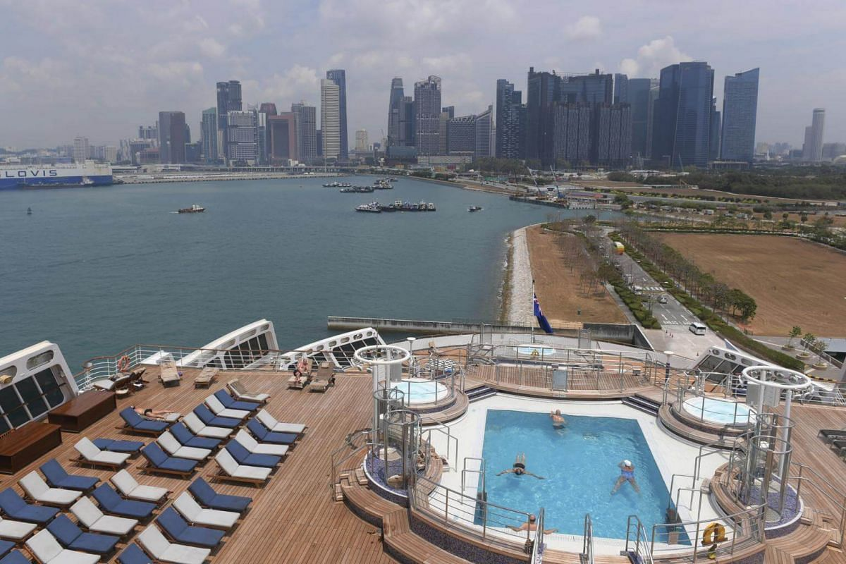 Guests relax and sun bath on the Queen Mary 2 oceanliner ship docked in Marina Cruise Centre in Singapore, on March 11, 2019.