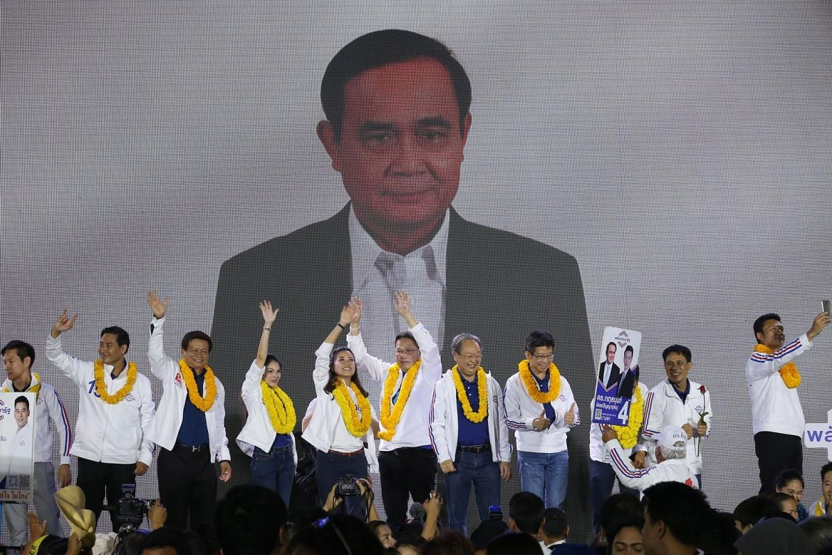 The Palang Pracharath's leader, Mr Uttama Savanayana (centre), with the pro-junta party's parliamentary candidates in front of a picture of Prime Minister Prayut Chan-o-cha at an election campaign last week. Students overcome with excitement as Mr Th