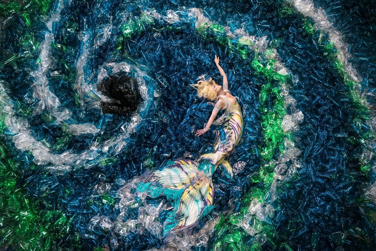 Sculptor Han Sai Por began her Black Forest installations (above) in response to the forest fires in Sumatra. The Mount That Keeps Growing by arts collective DPLMT. (Above) A photo of a mermaid surrounded by plastic bottles by Benjamin Von Wong is pa