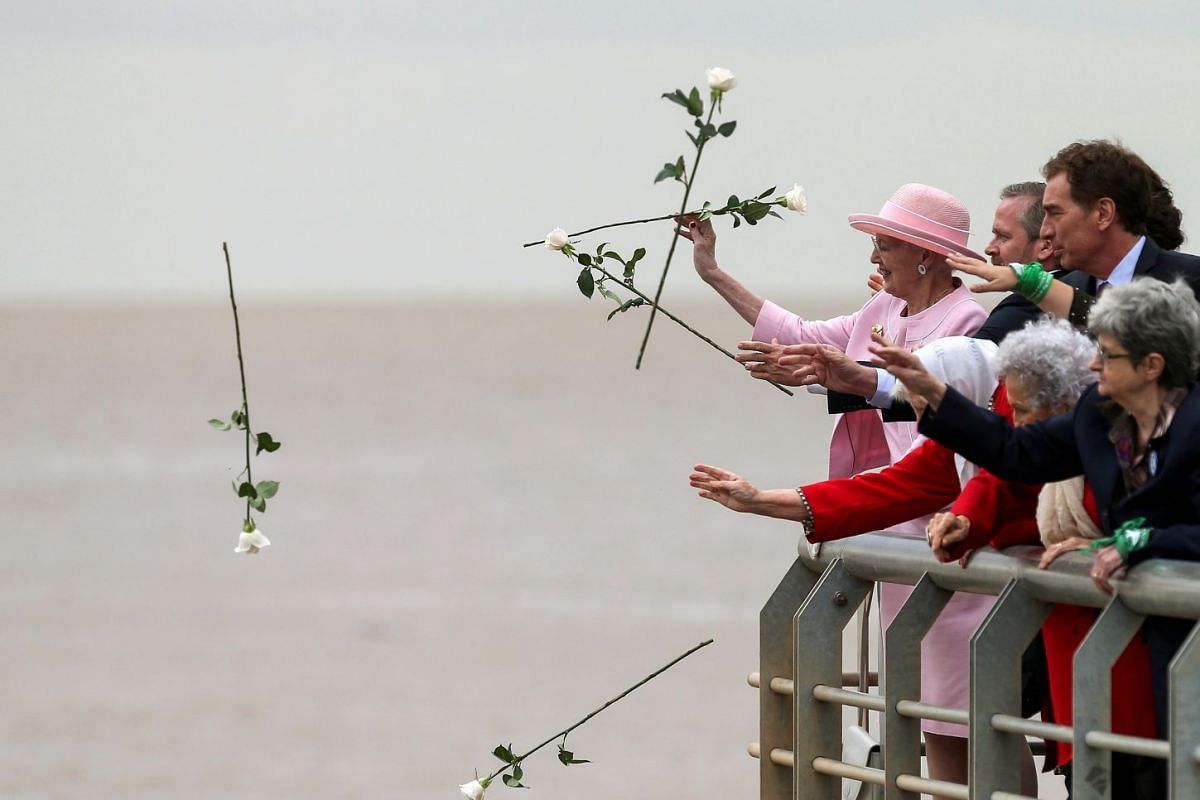 Queen Margrethe II of Denmark, throws flowers into the Rio de la Plata river next to members of Madres de Plaza de Mayo movement, to pay homage to the victims of Argentina's former dictatorship, in Buenos Aires, Argentina, March 19, 2019.