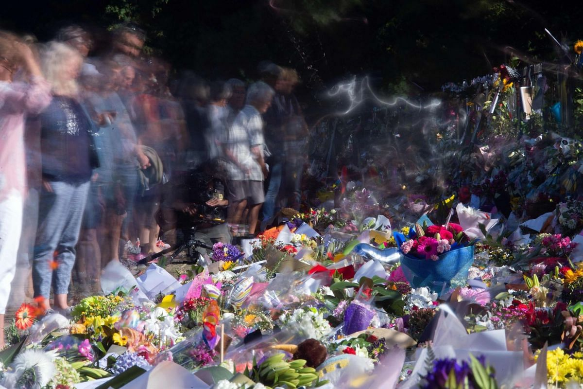Floral tributes to those who were gunned down at the two mosques are seen against a wall bordering the Botanical Garden in Christchurch on March 19, 2019. New Zealand Prime Minister Jacinda Ardern vowed never to utter the name of the twin-mosque gunm