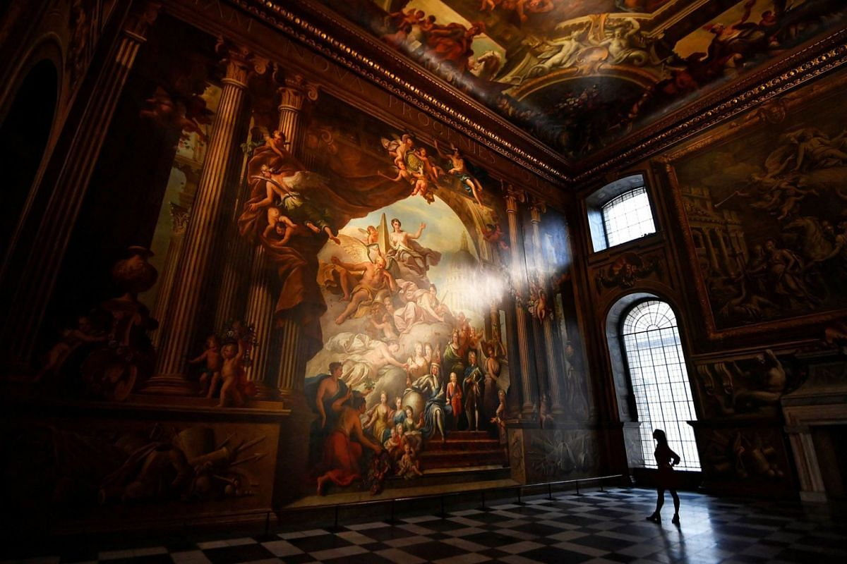 A gallery assistant poses beside a fresco during the reopening of The Painted Hall, Old Royal Navy College in London, Britain, March 20, 2019. PHOTO: REUTERS