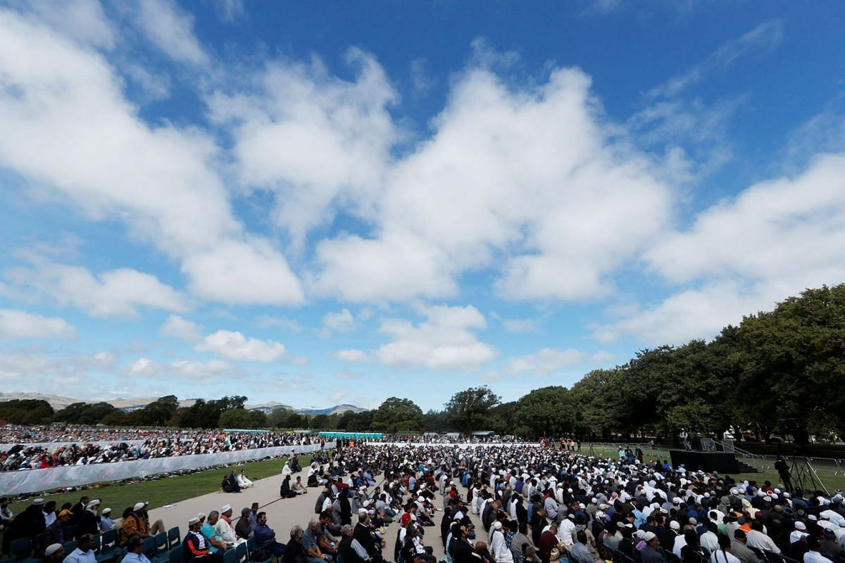 Thousands gather in a park opposite the Christchurch mosque where the killing spree took place a week ago, including Prime Minister Jacinda Ardern on Friday, March 22, 2019. The Muslim call to prayer was broadcast across New Zealand on Friday as the