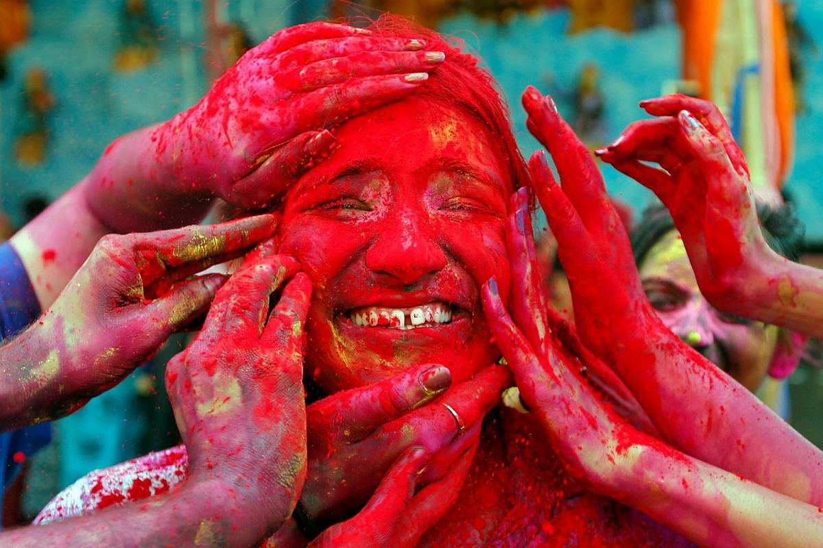 A woman reacts as devotees apply coloured powder on her face during celebrations for Holi outside a temple on the outskirts of Kolkata, India, March 21, 2019. PHOTO: REUTERS
