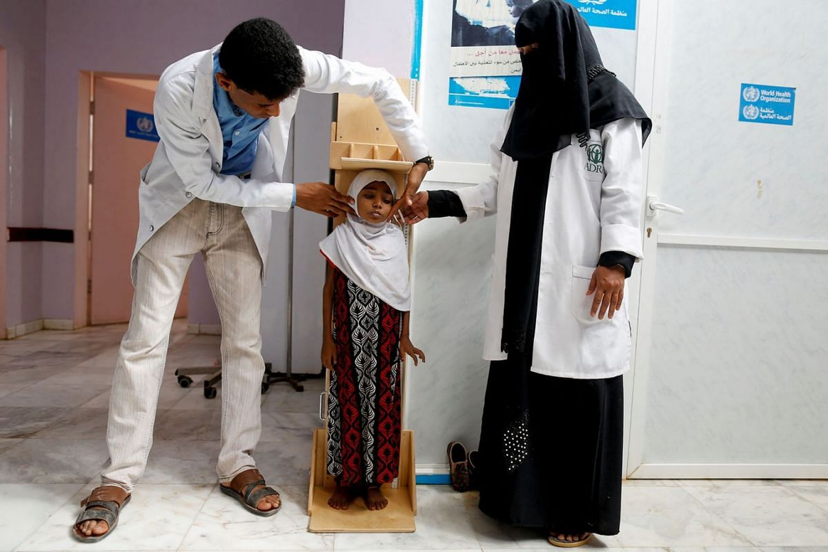 """Nurses measure the height of Afaf Hussein, 10, who is malnourished, at a clinic in Aslam, in the northwestern province of Hajjah, Yemen, February 17, 2019. Afaf, who now weighs around 11 kg and is described by her doctor as """"skin and bones"""", has been"""
