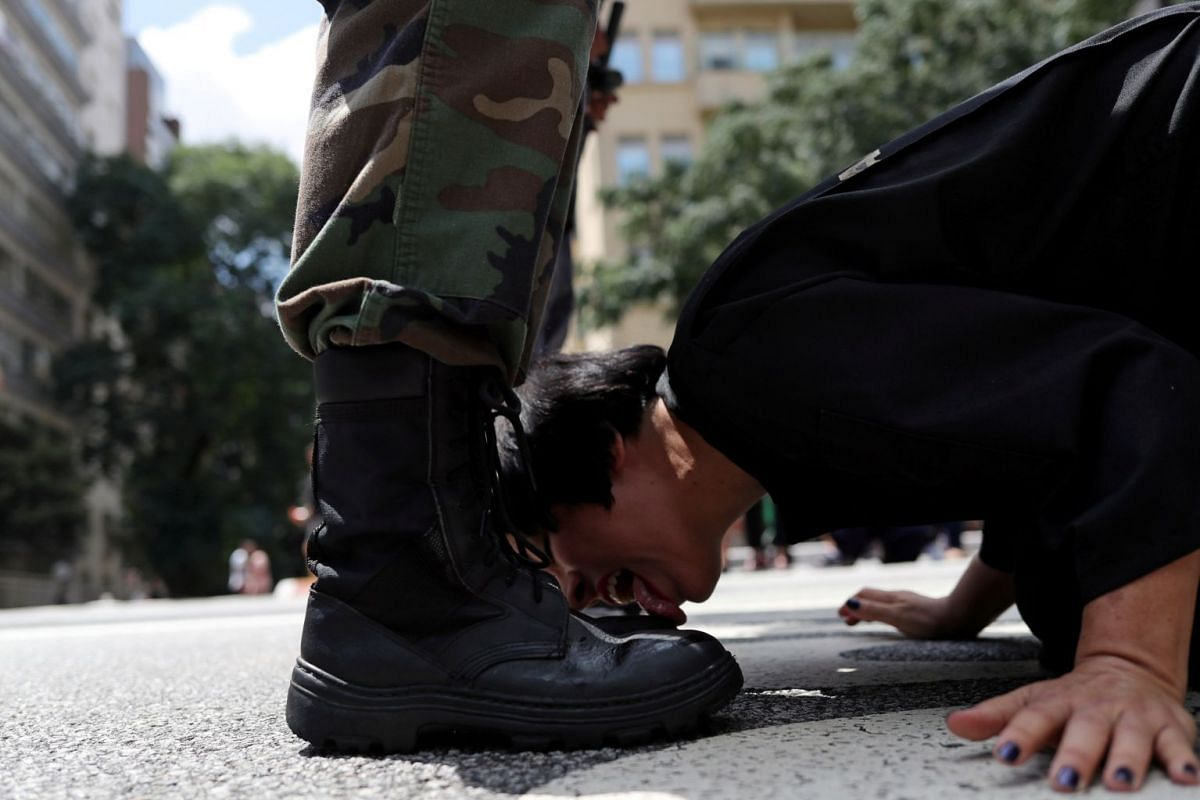 "Venezuelan artist Deborah Castillo licks the boots of a man dressed as a member of the military during her performance ""Lamebrasil, Lamezuela - questioning power in Latin America,"" in Sao Paulo, Brazil, March 24, 2019."