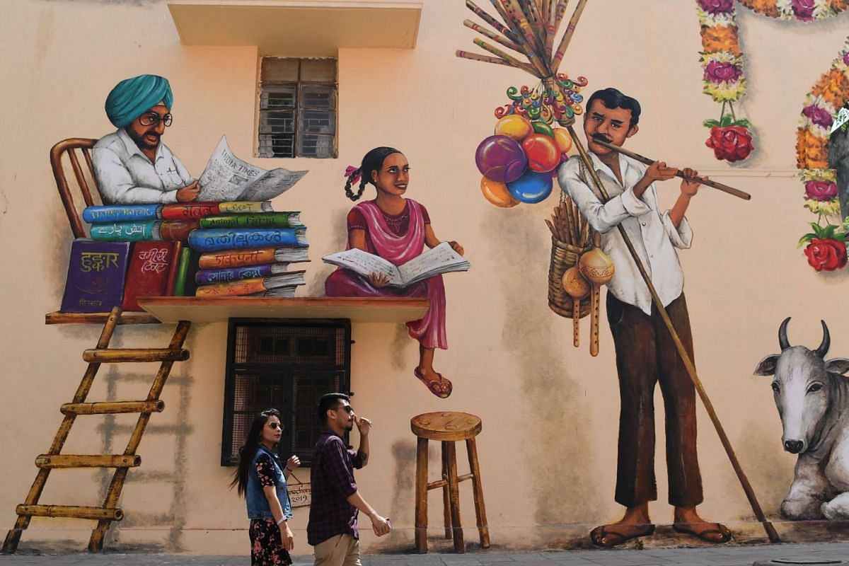 Indian onlookers walk past near murals at Lodhi Art District in New Delhi on March 24, 2019. Visitors throng Lodhi colony which has murals by dozens of Indian and international artists.