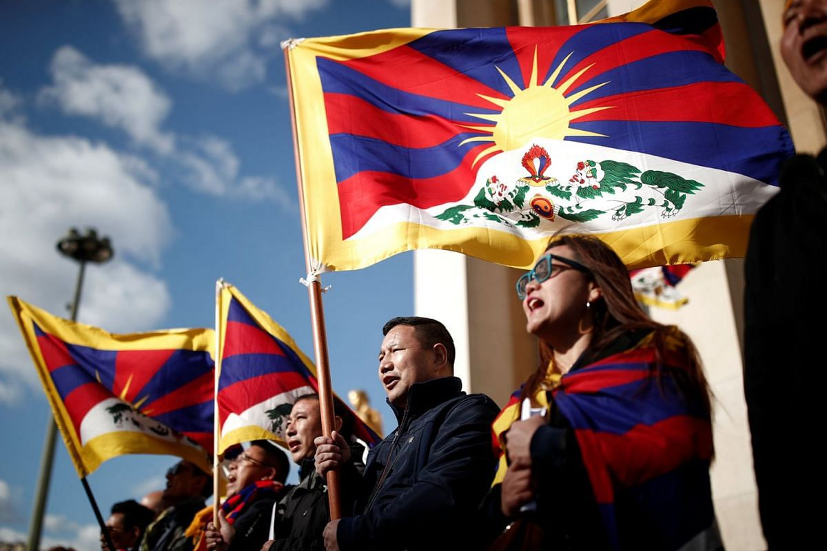 Protesters hold Tibetan flags during a demonstration over China's human rights record in front of the Eiffel Tower on the Trocadero esplanade in Paris, France, March 25, 2019.