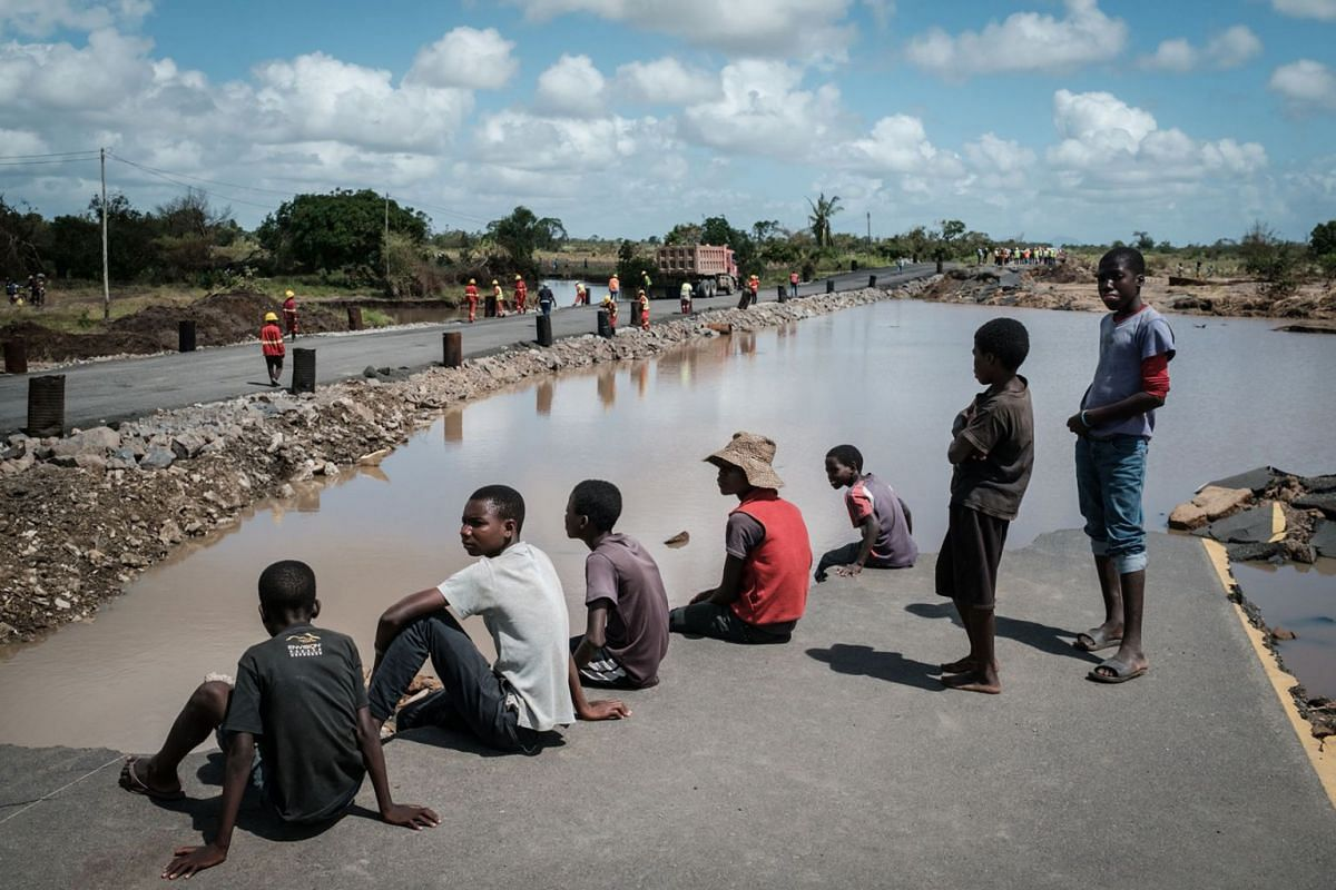 People watch the N6 road rebuilt in three days by China State Construction after the original road was destroyed by the Cyclone Idai in John Segredo, Mozambique, on March 24, 2019. Cyclone Idai smashed into Mozambique's coast unleashing hurricane-for