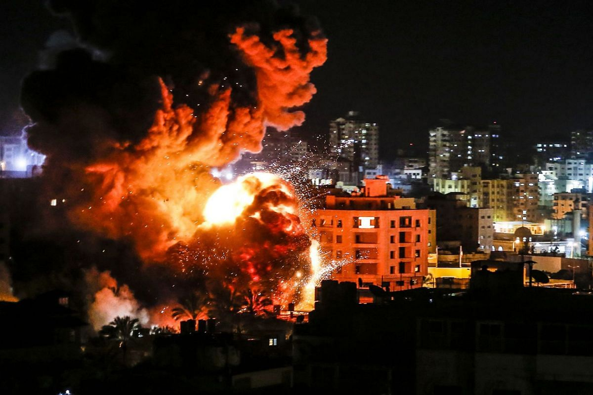 Fire and smoke billow above buildings in Gaza City during reported Israeli strikes on March 25, 2019. Israel's military launched strikes on Hamas targets in the Gaza Strip, the army and witnesses said, hours after a rocket from the Palestinian enclav