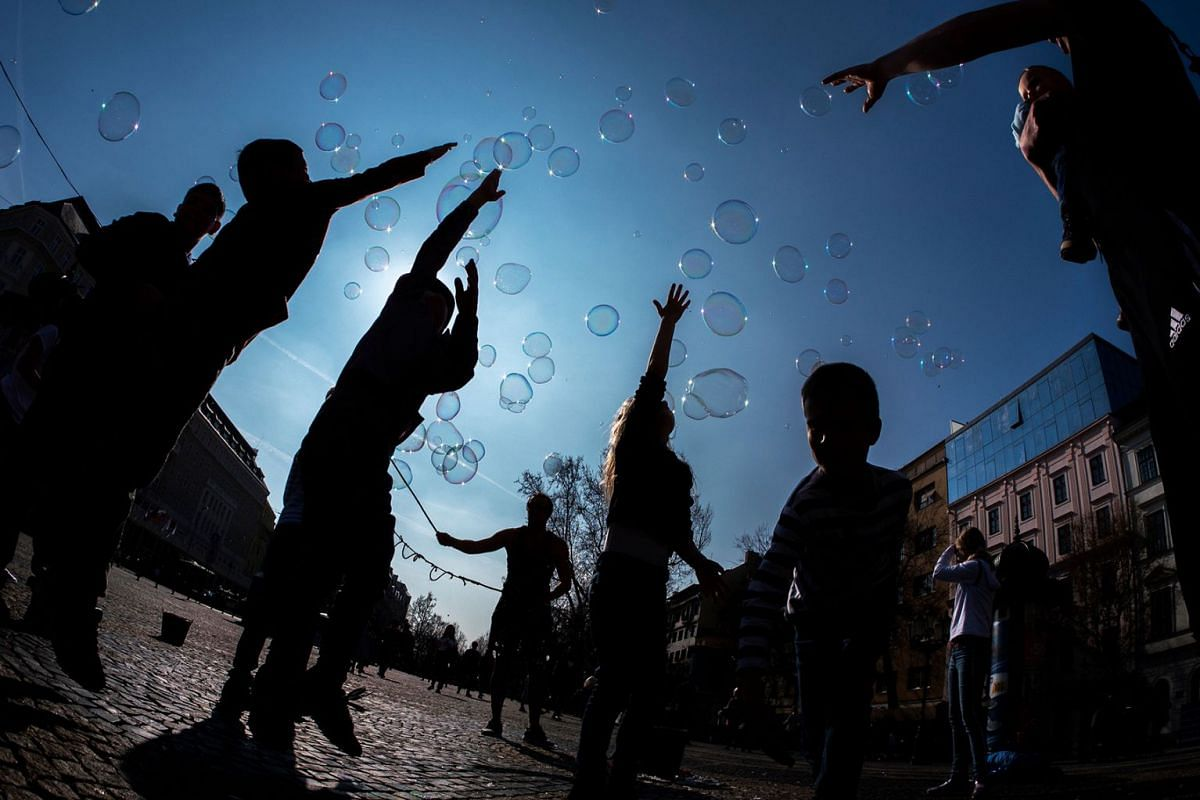 Children try to burst soap bubbles made by Polish busker Martin in front of the Slovak National Theatre in Bratislava, Slovakia on March 24, 2019.