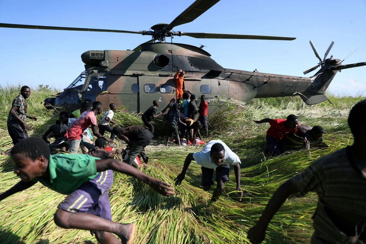 People run after collecting food aid from a South African National Defence Force (SANDF) helicopter in the aftermath of Cyclone Idai in Nhamatanda village, near Beira, Mozambique, March 26, 2019. PHOTO: REUTERS