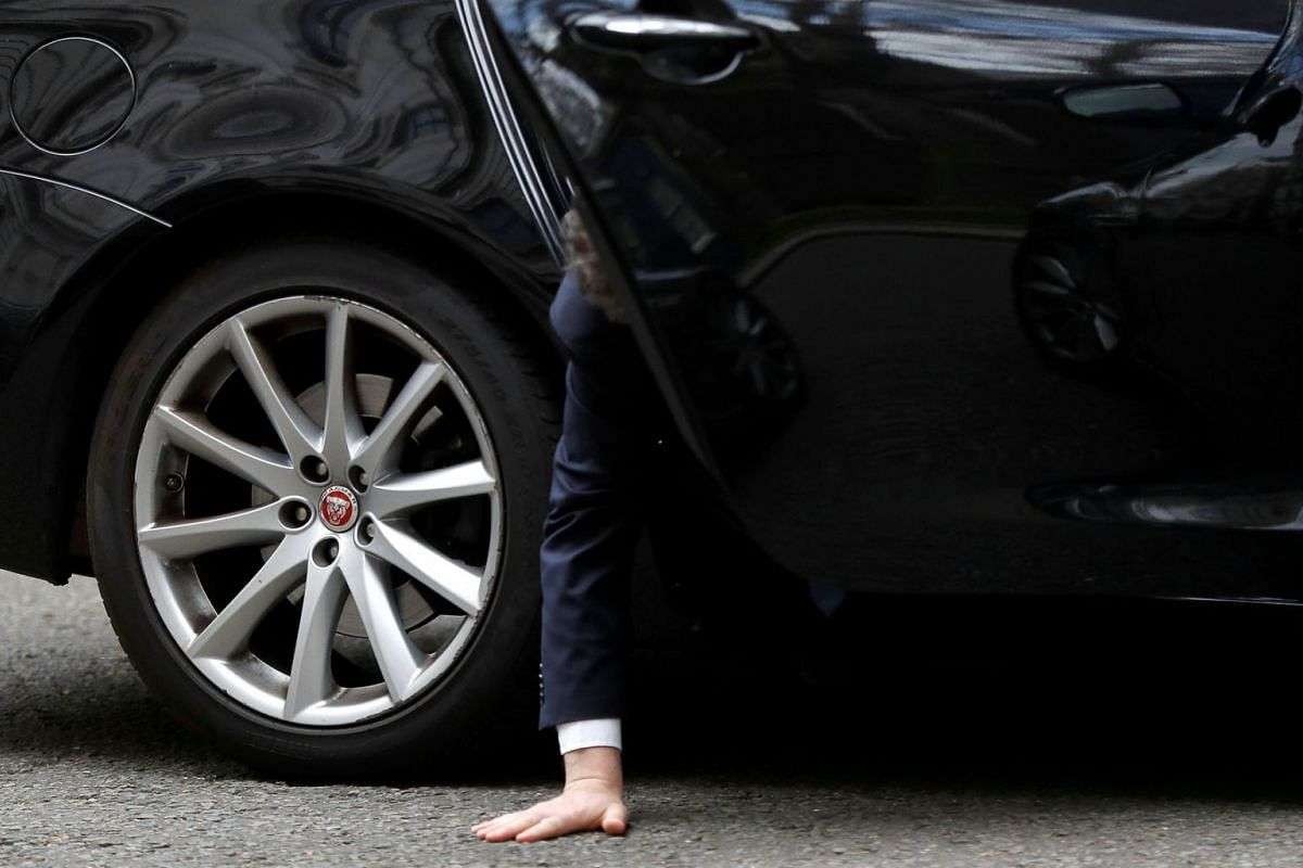 Britain's Conservative Party Chief Whip Julian Smith reaches for his dropped phone as he sits inside his car outside Downing Street in London, Britain, March 26, 2019. PHOTO: REUTERS
