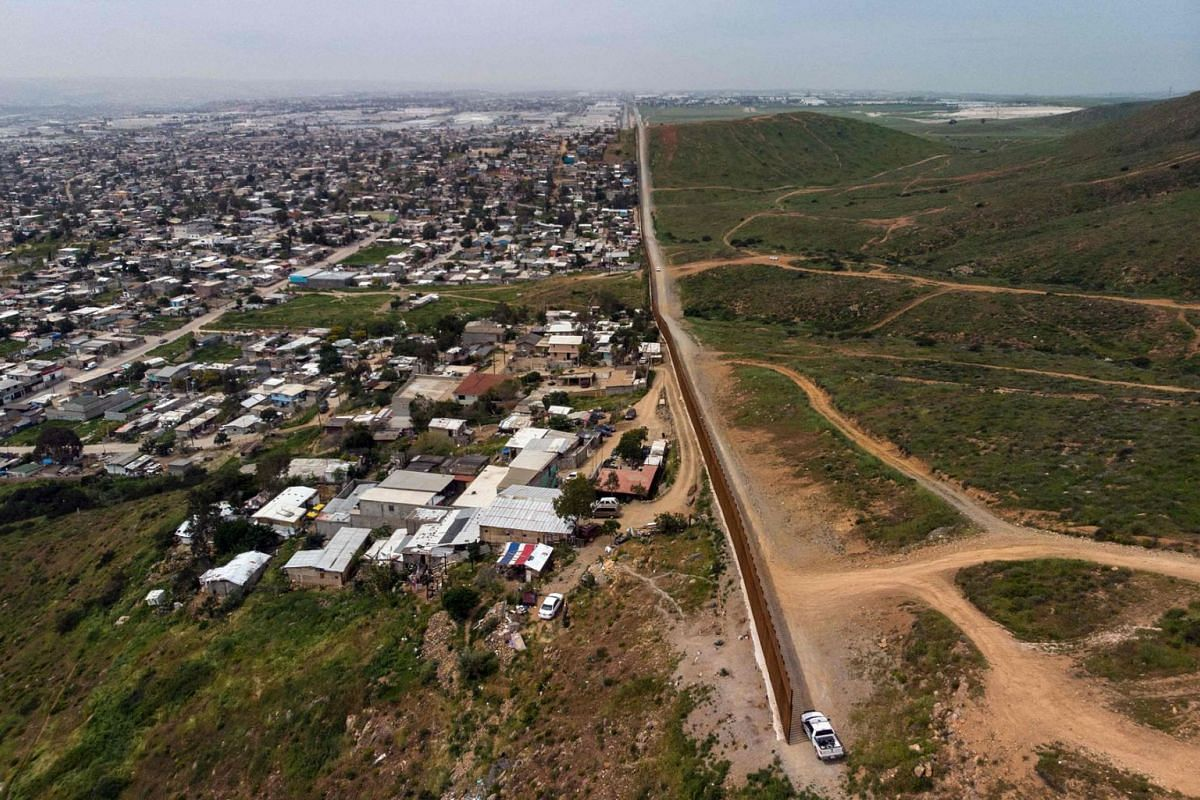 An aerial view of a Border Patrol unit next to a section of the US-Mexico border fence as it ends with Mexico on the left side and the United States on the right, at El Nido de las Aguilas, eastern Tijuana, Baja California state on March 26, 2019. A