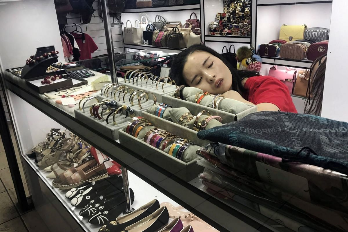 A salesgirl rests among Chinese manufactured shoes, bracelets and bags for sale at a shopping gallery known for selling cheap Asian products, along Paulista Avenue in Sao Paulo, Brazil, March 26, 2019. PHOTO: REUTERS