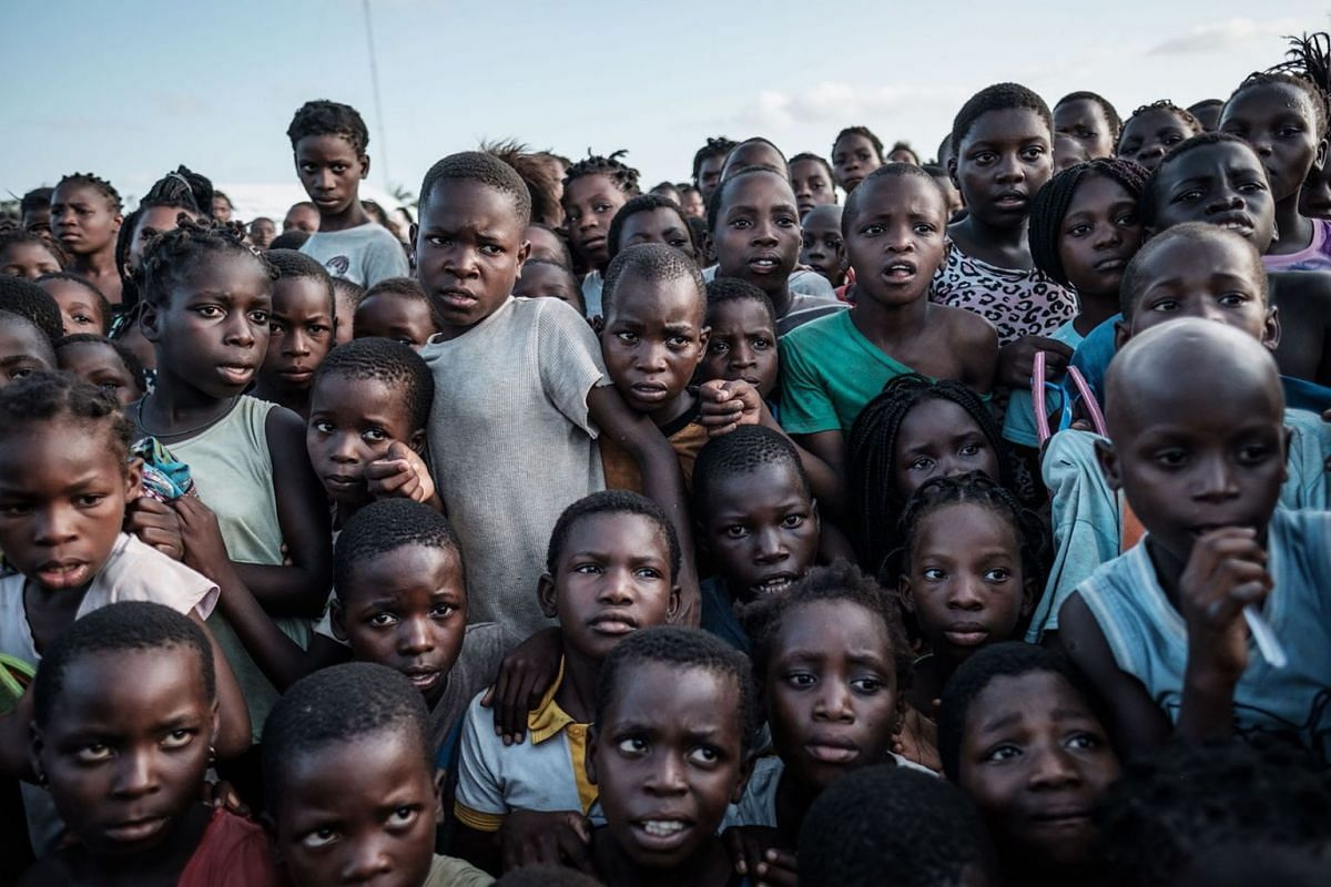 Children wait to receive food distribution from a local supermarket at an evacuation center in Dondo, about 35km north from Beira, Mozambique, on March 27, 2019. Five cases of cholera have been confirmed in Mozambique following the cyclone that ravag