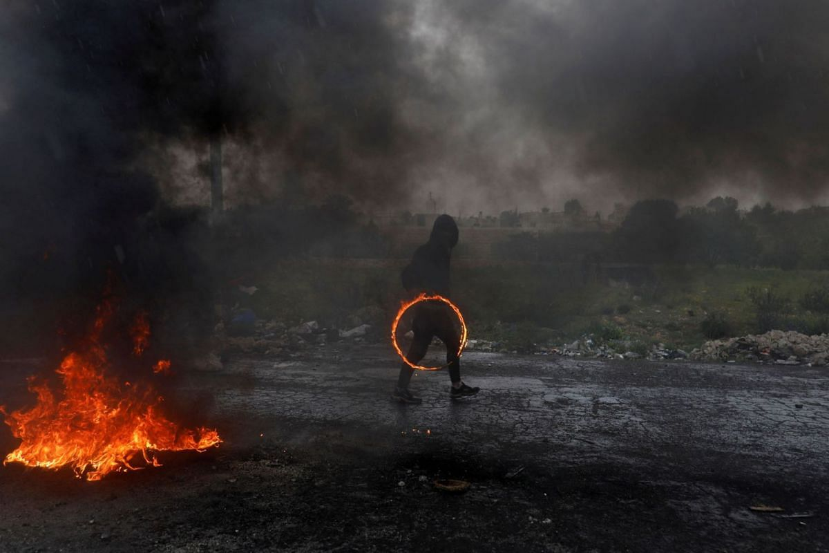 A Palestinian demonstrator holds a ring of fire during clashes with Israeli forces at a protest marking Land Day, near the Jewish settlement of Beit El, in the Israeli-occupied West Bank, March 30, 2019. PHOTO: REUTERS