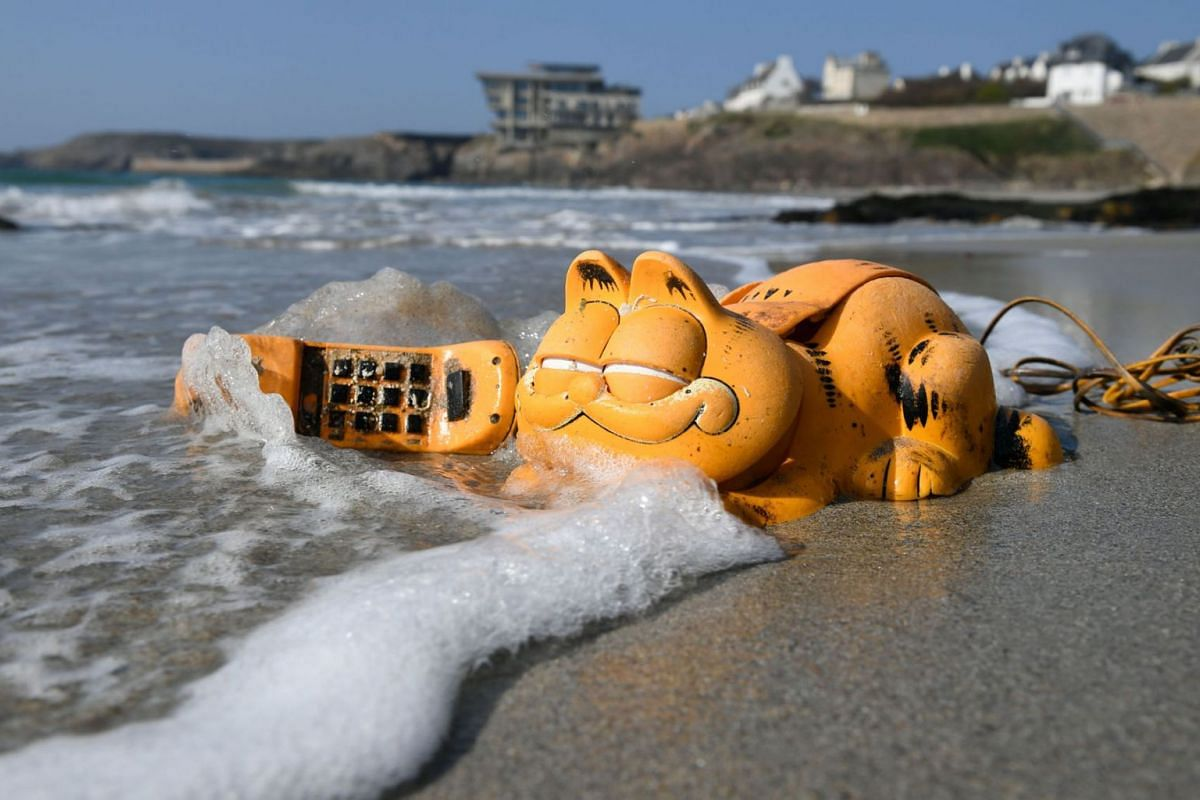 A plastic Garfield telephone on the beach on March 30, 2019, in Le Conquet, western France. For more than 30 years, plastic phones in the shape of the famous cat have been washing up on French beaches. The mystery is now solved: A shipping container