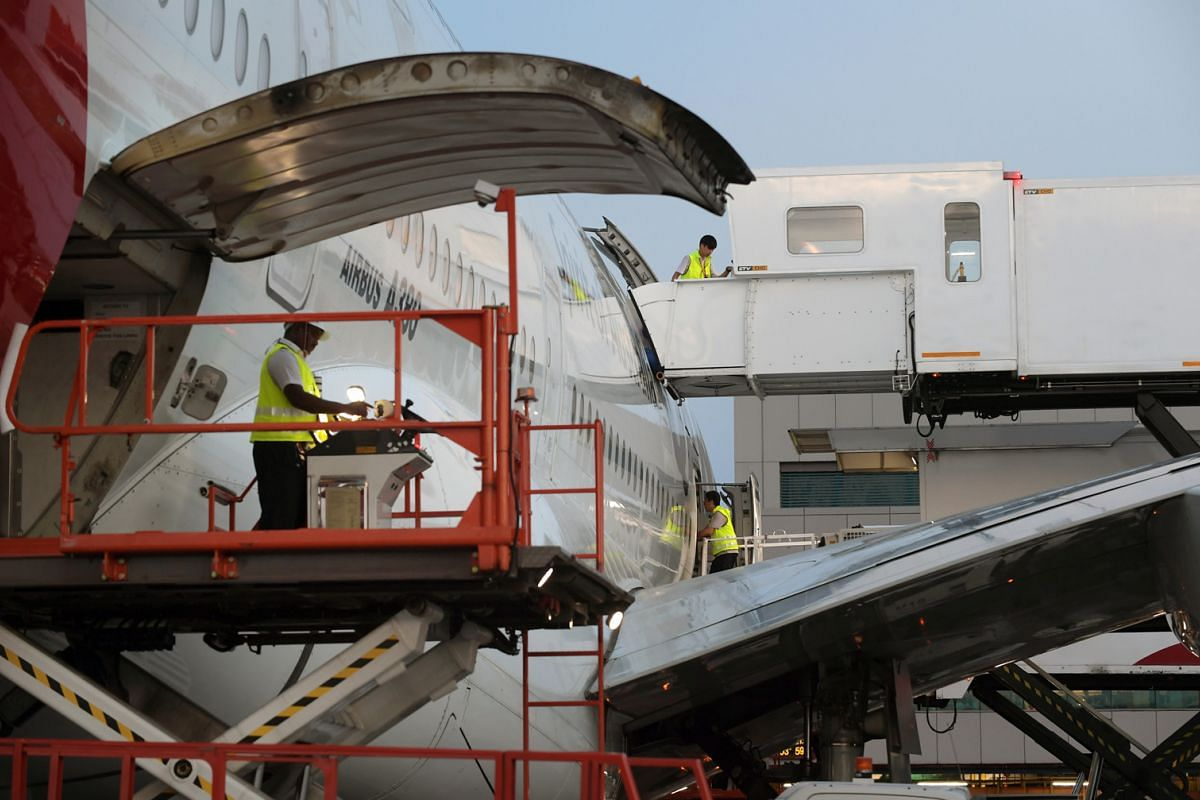 7.15PM: Joint container pallet loaders (above) are used to load meal carts and other containers that carry items such as luggage, freight and mail onto the double-decker jet. More than 80 galley carts of food are brought in. At one section of the air