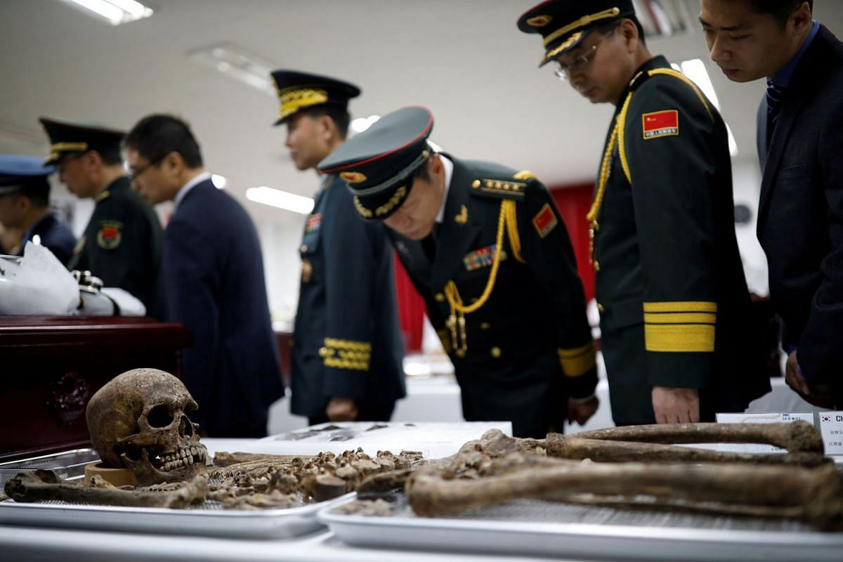 Chinese military officials look at the remains of a Chinese soldier who fought in the Korean War, during the coffin rites in Incheon, South Korea, April 1, 2019. PHOTO: REUTERS
