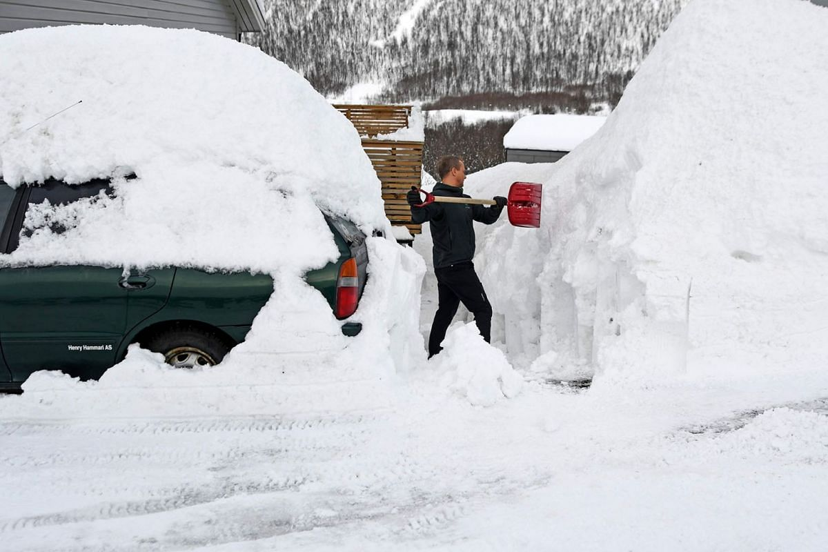 Hans Otto Larsen clears snow in front of his house in Tromso, Norway, April 1, 2019. PHOTO: AFP