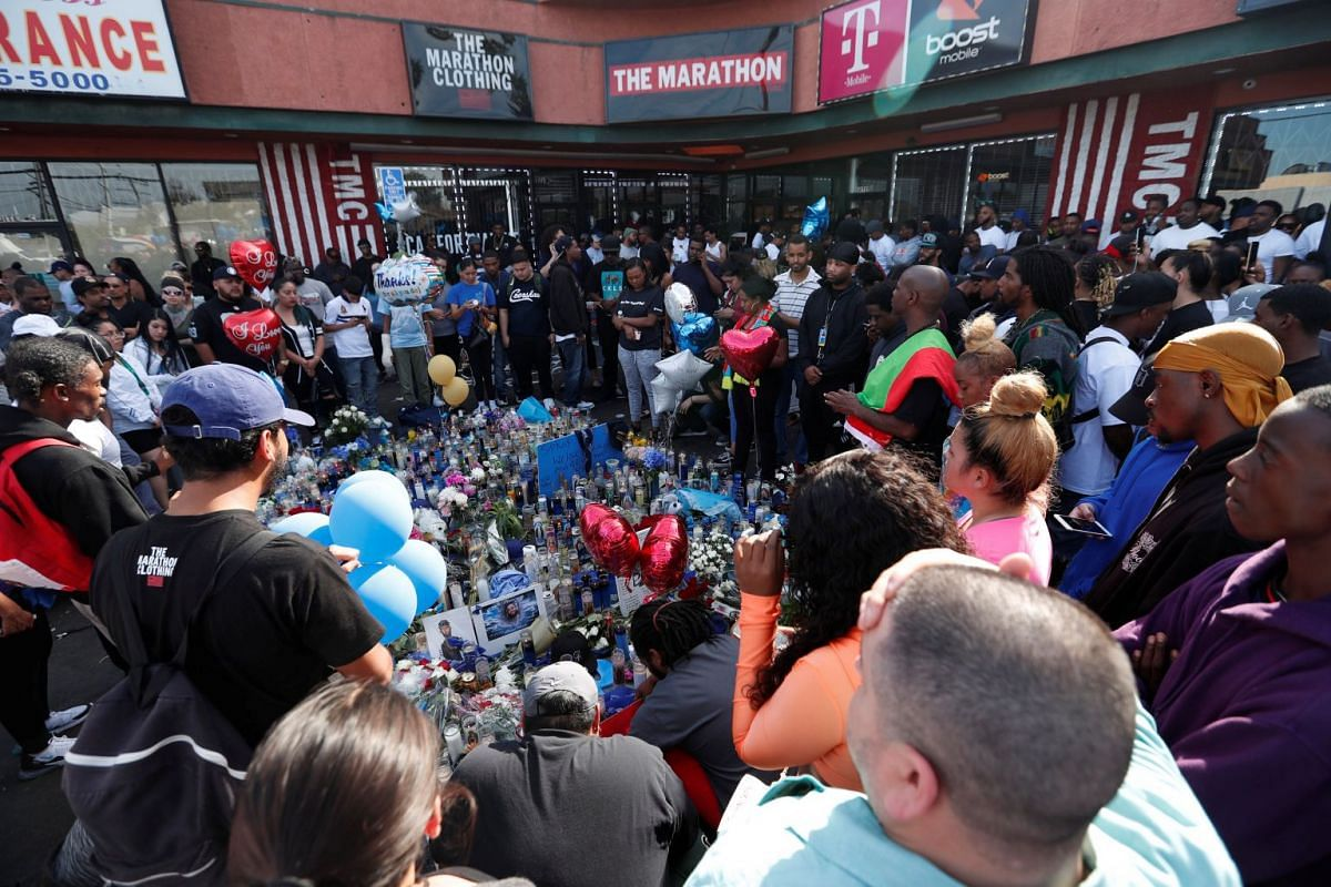 People gathering around a makeshift memorial for rapper Nipsey Hussle.