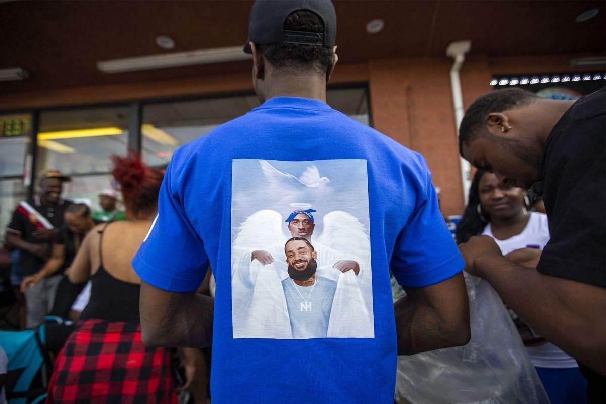 A T-shirt showing Nipsey Hussle (front) and slain rapper Tupac Shakur in heaven.